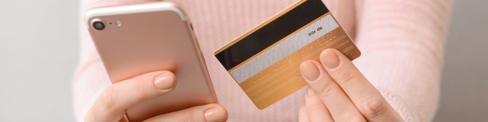 An unseen person in a pale pink sweater holds a pink smartphone in one hand and a credit card in the other.